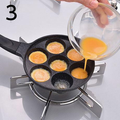 バターが溶けて、ふつふつと音をたてはじめたら、卵を各穴に均等(穴の6分目くらい)に流し入れる。